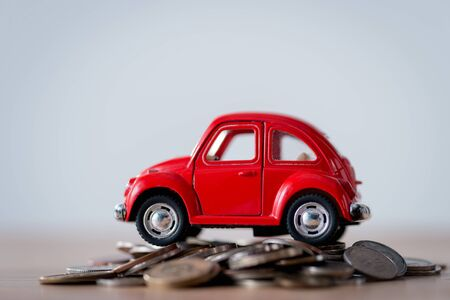 red toy car on metal coins on wooden surface isolated on grey