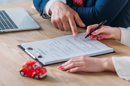 cropped view of car deal pointing at signature place in loan agreement near woman holding pen Stock Photo