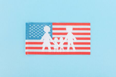 top view of paper cut white family on national american flag on blue background Banque d'images - 125406420