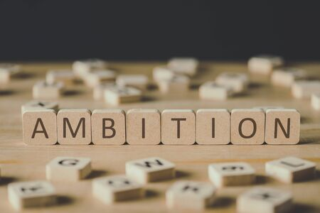 selective focus of cubes with word ambition surrounded by blocks with letters on wooden surface isolated on black