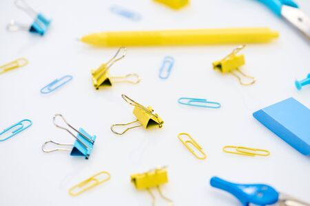 selective focus of colourful paper clips and other stationery on white background Foto de archivo - 125404345