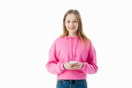 happy teenage girl in pink hoodie holding smartphone isolated on white
