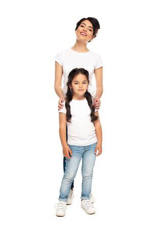 glückliche lateinische Mutter, die mit süßer Tochter isoliert auf weiß steht Standard-Bild