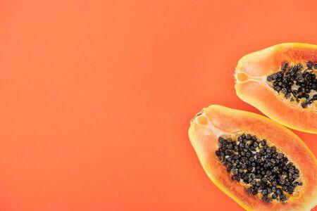 Draufsicht auf reife exotische Papayahälften mit schwarzen Samen isoliert auf Orange mit Kopierraum with