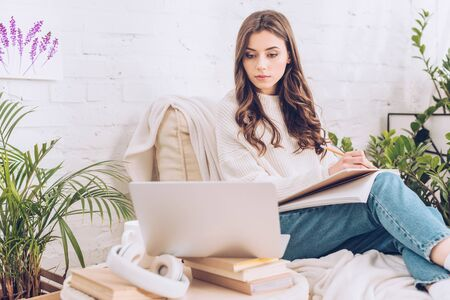 beautiful young woman writing in notebook and using laptop at home
