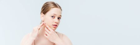 upset teenage girl touching pimple on face, panoramic shot