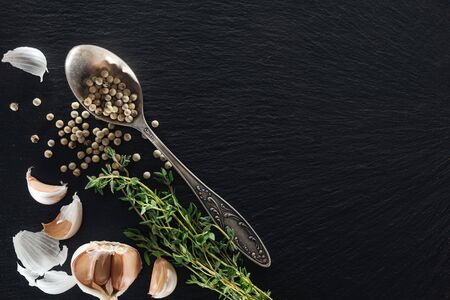 top view of white pepper in silver spoon near garlic cloves and green herb Banco de Imagens