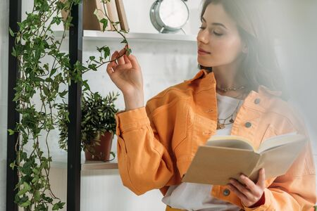 selective focus of pensive young woman holding book and touching plant while standing bu rack Banco de Imagens