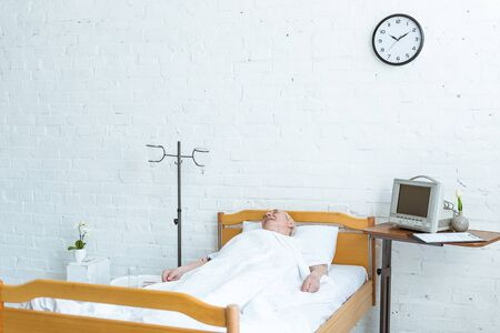 senior patient lying on bed in hospital ward Stock Photo