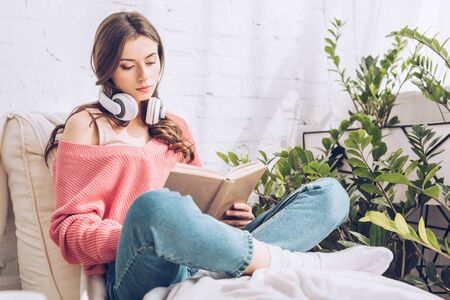 attentive woman with headphones on neck reading book while sitting with crossed legs