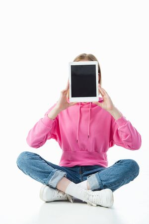 teenage girl in lotus pose holding digital tablet with blank screen isolated on white