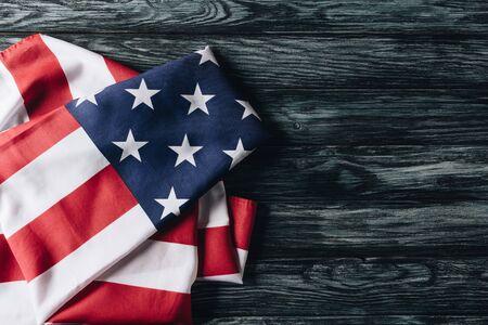 Bandera doblada de los Estados Unidos de América sobre la superficie de madera gris, concepto del Día de los Caídos