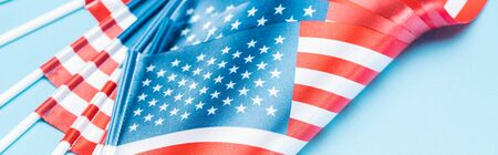 close up view of silk usa flags on sticks on blue background, panoramic shot
