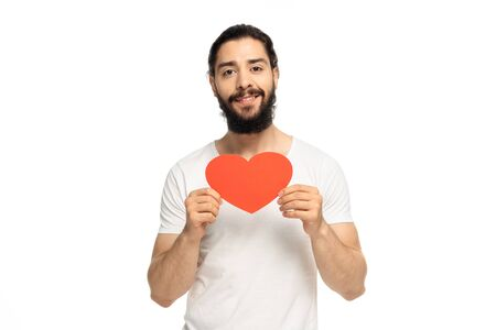 happy latin man holding red heart-shape carton isolated on white