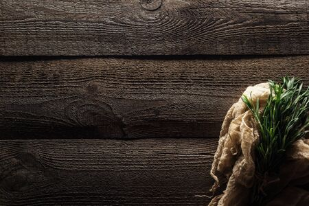 top view of green rosemary in cotton rustic cloth on wooden weathered table with copy space Stock Photo