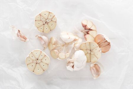 top view of cut garlic cloves on white paper background