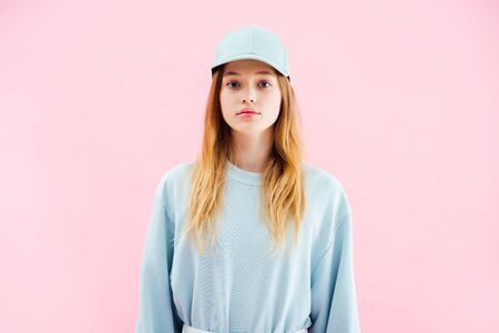 sad pretty teenage girl in cap looking at camera isolated on pink