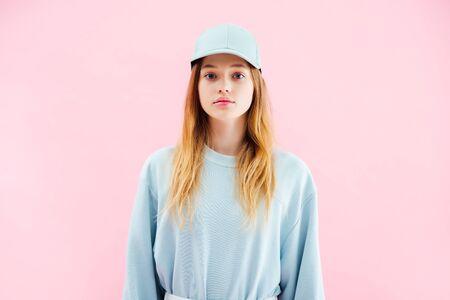 triste, jolie adolescente, dans, casquette, regarder appareil-photo, isolé, sur, rose