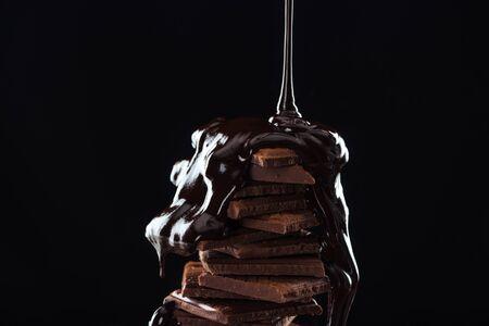 Hete gesmolten chocolade gieten op chocolade stapel, geïsoleerd op zwart