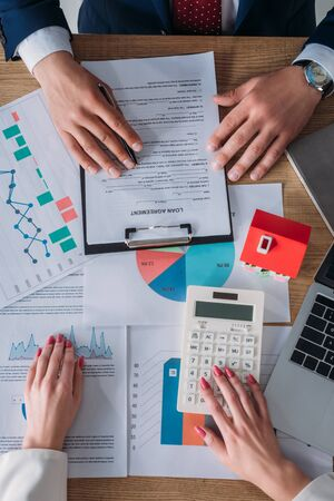 partial view of customer reading loan agreement and businesswoman using calculator while sitting at workplace near laptop, house model, graphs and charts