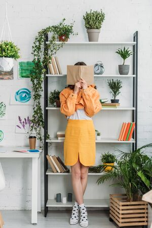 fashionable young woman standing bu rack and hiding face behind book
