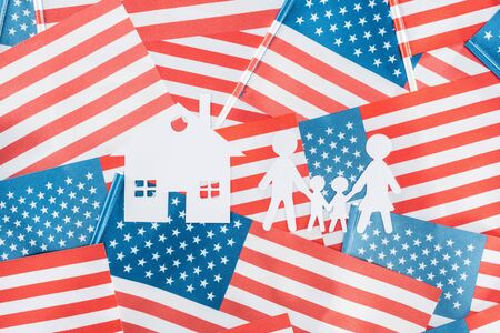 top view of white paper cut house and family on american flags background Stock Photo - 125402132