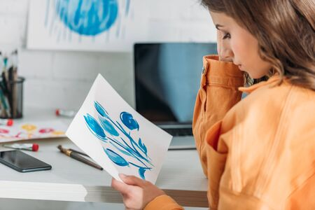 pensive young woman sitting at desk and looking at painting with blue flowers Stock Photo