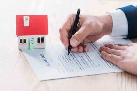 Teilansicht des Maklers, der im Kreditvertrag in der Nähe des Hausmodells auf einer Holztischplatte schreibt Standard-Bild