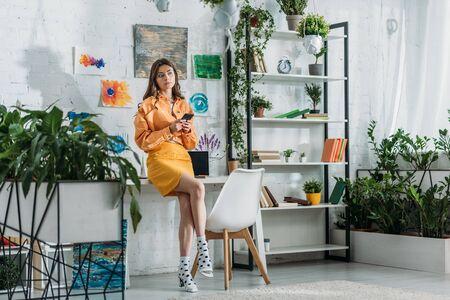 stylowy grl za pomocą smartfona w przestronnym pokoju ozdobionym zielonymi roślinami i kolorowymi obrazami na ścianie