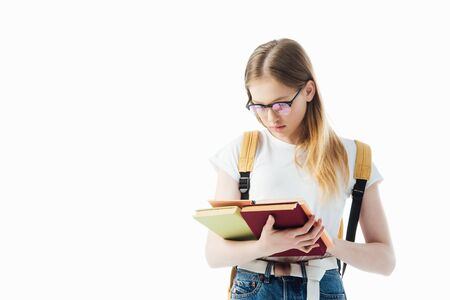schoolgirl in glasses with backpack reading book isolated on white Banque d'images