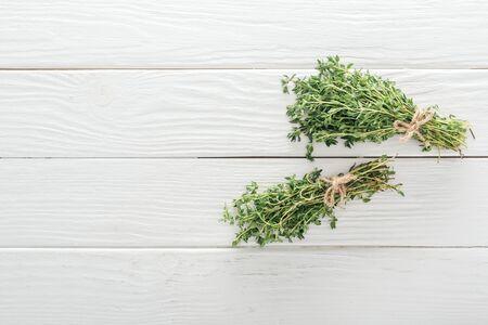 vue de dessus du thym vert frais sur une surface en bois blanche