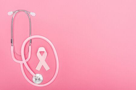top view of pink stethoscope and breast cancer symbol on pink background with copy space