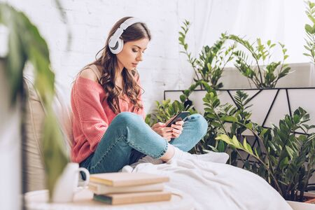 selective focus of pensive young woman sitting with crossed legs, listening music in headphones and using smartphone