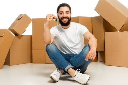 bearded latin man holding key and sitting with crossed legs near boxes isolated on white