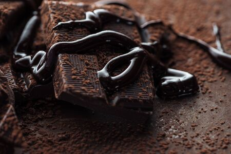 Close up view of chocolate bar with melted chocolate and cocoa powder