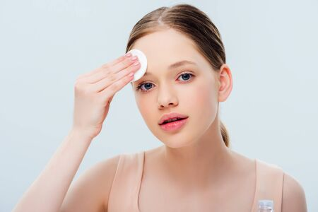 beautiful teenage cleansing face with cotton pad isolated on grey Stock Photo