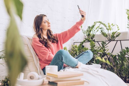 selective focus of smiling young girl taking selfie with smartphone while sitting with crossed legs on soft chaise lounge