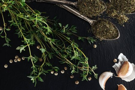 top view of dried thyme in silver spoons near green herb, white pepper and garlic cloves on black background Banco de Imagens