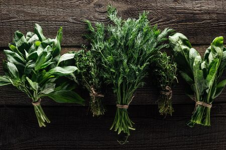 top view of green thyme, spinach, basil and dill on wooden weathered table