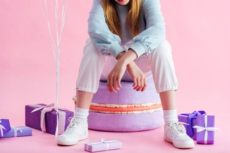 cropped view of teenage girl sitting on decorative macaroon near presents on pink