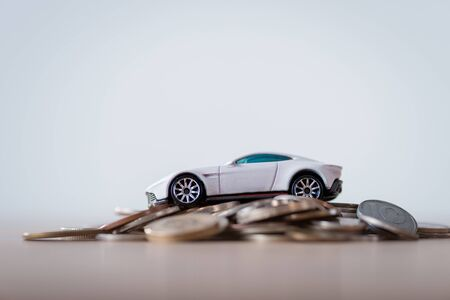 miniature car on metal coins on wooden surface isolated on grey Stock Photo