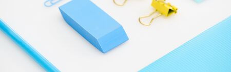 panoramic shot of blue paper clip, eraser, pencil, folder and yellow paper clips isolated on white