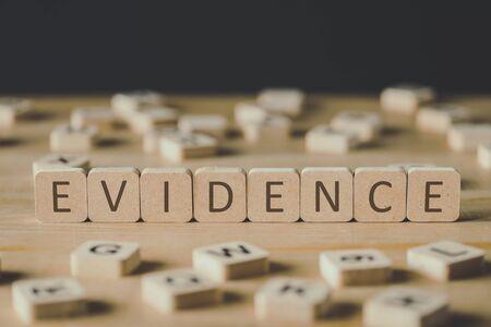 El enfoque selectivo de la palabra evidencia hecha de cubos rodeados por bloques con letras sobre la superficie de madera aislado en negro