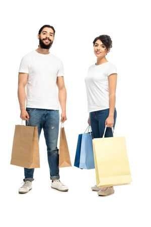 happy latin man and woman holding shopping bags while standing isolated on white Foto de archivo