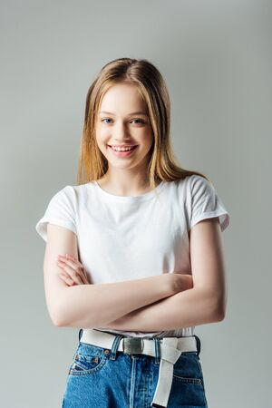 happy teenage girl with crossed arms looking at camera isolated on grey