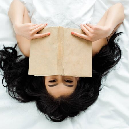 Top view of Asian woman covering face with book while lying on bed Stock fotó
