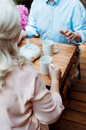 Cropped view of senior couple sitting near teapot and cups