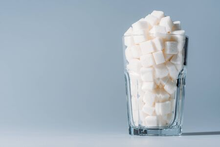 Glass full of refined white sugar cubes on grey background with copy space