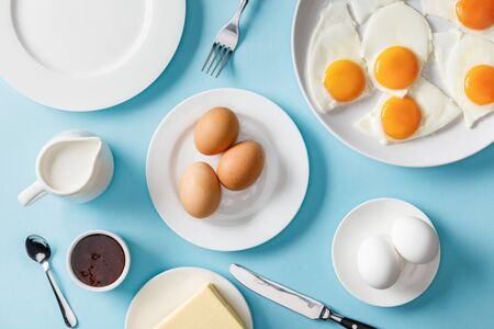Top view of served breakfast with empty plate on blue background