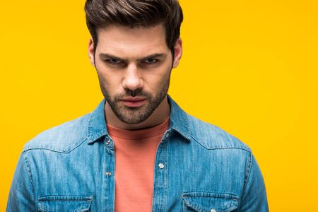 Handsome aggressive man looking at camera isolated on yellow background